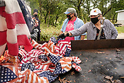 12 SEPTEMBER 2020 - DES MOINES, IOWA: DAVID HOTT and BETH STEVEN throw US flags into the fire during a flag retirement ceremony at Glendale Cemetery in Des Moines. About 10 volunteers came to the cemetery Saturday morning to properly dispose of about 4,000 American flags. The flags had flown over veterans' graves, local businesses, and state offices. The US Flag Code calls for used American flags to be respectfully disposed of in a fire.   PHOTO BY JACK KURTZ