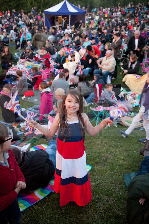 © Licensed to London News Pictures. 04/06/12. Maidstone, Kent. Child waving flags whilst waiting for one of the 4000 beacons to be lit to celebrate Her Majesty The Queen's Diamond Jubilee at Whatman Millenium Park, Maidstone, Kent.The Royal Jubilee celebrations, Great Britain is celebrating the 60th anniversary of the countries Monarch HRH Queen Elizabeth II accession to the throne this weekend. Picture credit should read Manu Palomeque/LNP