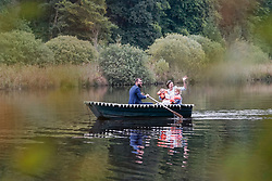 Bridal groom with children traveling in boat on lake, Bavaria, Germany