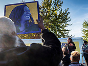 12 OCTOBER 2019 - DES MOINES, IOWA: A man holds up a photo of Sen. Harris while Senator KAMALA HARRIS (D-CA) speaks to a crowd of about 150 people at a Des Moines block party Saturday. Sen. Harris attended a neighborhood block party in Des Moines as a part of her campaign to be the Democratic nominee for the US presidency in 2020. Iowa traditionally holds the first selection of the presidential election cycle. The Iowa caucuses are Feb. 3, 2020.        PHOTO BY JACK KURTZ