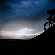 Malachi Artise silhouetted against a summer thunderstorm along a ridge on his mountain bike in the Tetons.