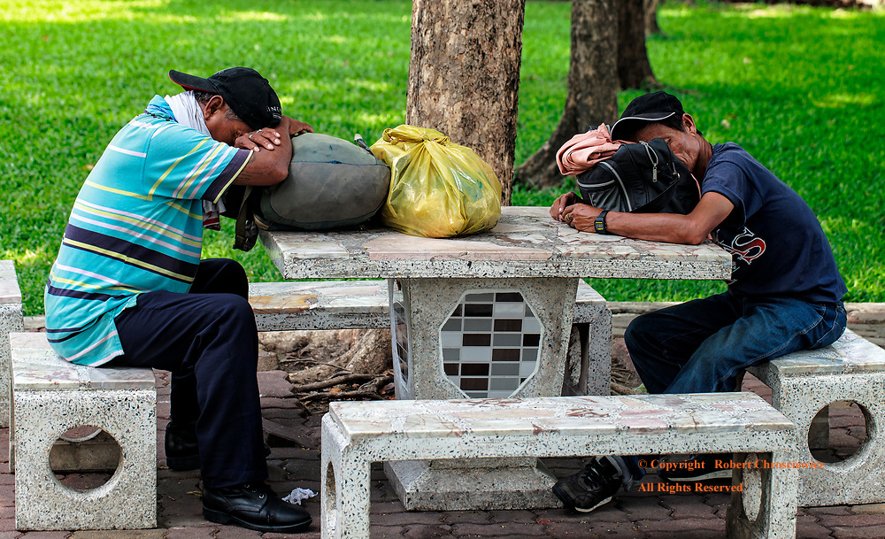 Friends of Necessity: Two men, with their pocessions, find refuge and a quiet moment to nap in a central city park, Bangkok Thailand.