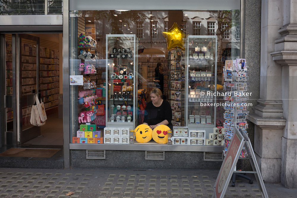 Smiley face cushions in a shop window are arranged by a shop employee in central London.