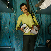 Peddler selling Books.<br /> Throughout the journey, peddlers pop into the train compartments with all sorts of offerings,  to be bargained for a few rupees.<br /> Inside the Dibrugarh-Kanyakumari Vivek Express, the longest train route in the Indian Subcontinent. It joins Kanyakumari, Tamil Nadu, which is the southernmost tip of mainland India to Dibrugarh in Assam province, near the border with Burma.
