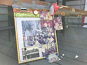 framed photo of Preacher from atop stolen meat counter – adorned with beads, hair ties and other photos17x22 in photos with 3 ft of decorated wood<br />
