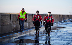 © Licensed to London News Pictures. 13/01/2017. Jaywick, UK. Members of a search and rescue team walk along flood defences on the seafront at Jaywick, Essex, where homes were expected to be evacuated due to the threat of flooding in low-lying areas . Photo credit: Ben Cawthra/LNP