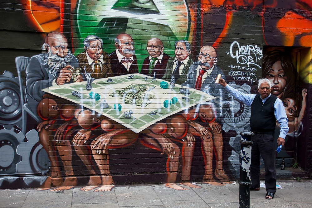 """London, UK. Friday 5th September 2012. 'Freedom for Humanity' a street art graffiti work by artist Mear One aka Kalen Ockerman on Hanbury Street near Brick Lane. Tower Hamlets has ordered that the mural be removed as the characters depicted as bankers have faces that look Jewish, and is therefore antisemitic. In protest the mural had just been sprayed with the Hebrew word 'HAGANAH'. Haganah was a Jewish paramilitary organization in what was then the British Mandate of Palestine from 1920 to 1948, which later became the core of the Israel Defense Forces. Local businessman (pictured), and owner of the wall Azmal Hussein said """"This is not anti-Semitic. This is my wall, my property, and I don't want it to go."""""""