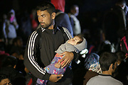 A migrant holds his child during a stand off with police close to the Hungarian and Serbian border town of Roszke, Hungary, September 8 2015. The UN's humanitarian agencies are on the verge of bankruptcy and unable to meet the basic needs of millions of people because of the size of the refugee crisis in the Middle East, Africa and Europe, senior figures within the UN have told the media.