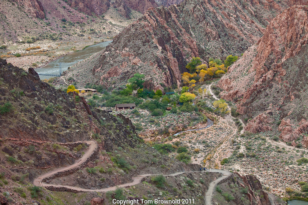 The South Kaibab Trail winding down towards the Colorado River in Grand Canyon and Bright Angel Canyon across the way. The Schist and Quartzite complimenting the Cottonwood trees the entice the hike towards Phantom Ranch.