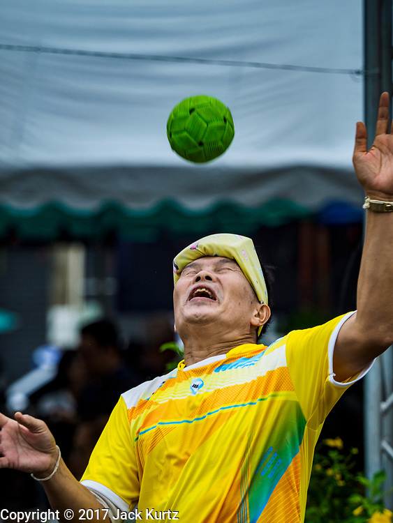 04 OCTOBER 2017 - CHONBURI, CHONBURI, THAILAND: A man playing takraw before the water buffalo races. Contestants race water buffalo about 100 meters down a muddy straight away. The buffalo races in Chonburi first took place in 1912 for Thai King Rama VI. Now the races have evolved into a festival that marks the end of Buddhist Lent and is held on the first full moon of the 11th lunar month (either October or November). Thousands of people come to Chonburi, about 90 minutes from Bangkok, for the races and carnival midway.   PHOTO BY JACK KURTZ