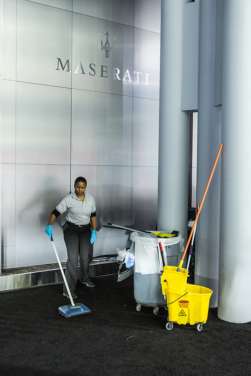 New York, NY, USA-23 March 2016. A woman cleaning the carpeting behind the Maserati stand at the New York Auto Show. Cleaners were continually at work throughout the show.