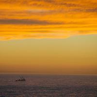 A fishing boat sails through a Pacific Ocean sunset off the California coast near San Francisco.
