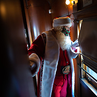 """STRASBURG, PA:  Dave Saunders, 46<br /> in his 7th year as Santa, looks out the window before greeting passengers riding a holiday attraction """"Santa Express, on the oldest continually operated railroad in the country, in Strasburg, PA on December 13, 2020. The pandemic has forced difficult decisions about maintaining the holiday tradition of visits to Santa Claus versus safety concerns.  Plexiglass dividers, face shields, and physical distancing are among the precautions for those locations that have proceeded with Santa photo opportunities.  CREDIT:  Mark Makela for The New York Times"""
