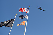 East Meadow, New York, USA. May 25, 2019. A U.S. Navy MH-53E helicopter flies over flagpoles with the American Flag, POW-MIA flag, and Nassau County flag in Veterans Memorial Plaza, as the aircraft departs after being on display as part of Fleet Week, on Saturday of Memorial Day Weekend at Eisenhower Park on Long Island.