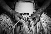 """2015/03/13 - Pile, Ecuador: Detail of Mariana Rivera, 73, hands weaving a """"Montecristi hat"""" in her house early in the morning. She started to weave hats at the age of 10. Nowadays she doesn't weave the finest hats as before because her eyes are tired and old as she says. So, Mariana uses thicker straw to weave a hat, which brings the price down. She sells them at around US$200, but sometimes even less if she is really desperate for money.  UNESCO declared the """"Montecristi hat"""" in 2012 as Intangible Cultural Heritage of Humanity."""
