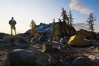 A silohuetted man watching the sun rise over his camp site in the Upper Enchantments, Cascade Range, Washington, USA.