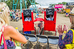Performers mime to pop songs in small red boxes. The 2015 Glastonbury Festival, Worthy Farm, Glastonbury.