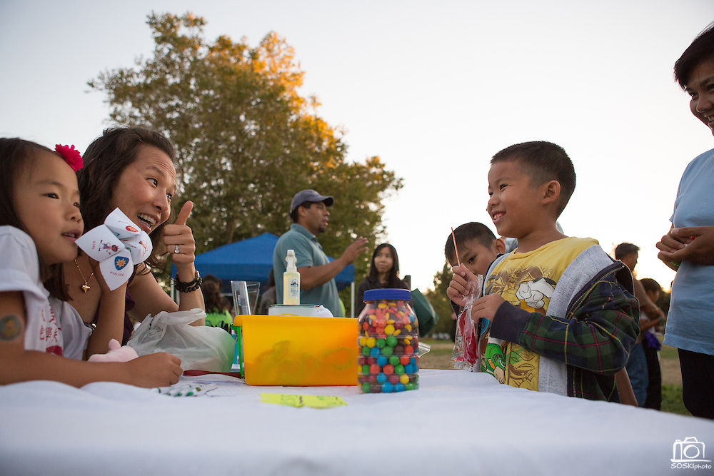 Children guess the number of M&Ms in the jar amongst other games during National Night Out at Berryessa Creek Park in San Jose, Calif., on Aug. 7, 2012.  Photo by Stan Olszewski/SOSKIphoto.
