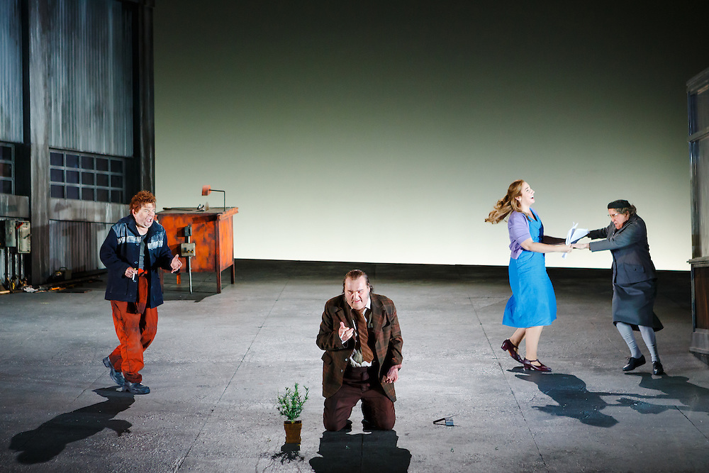 """LONDON, UK, 21 June, 2016. Left to right: Peter Hoare (as Laca Klemen), Graeme Danby (as Foreman), Laura Wilde (as Jenufa) and Valerie Reid (as Grandmother Buryja) rehearse for the revival of director David Alden's production of Janacek's opera """"Jenufa"""" at the London Coliseum for the English National Opera. The production opens on 23 June. Photo credit: Scott Rylander."""