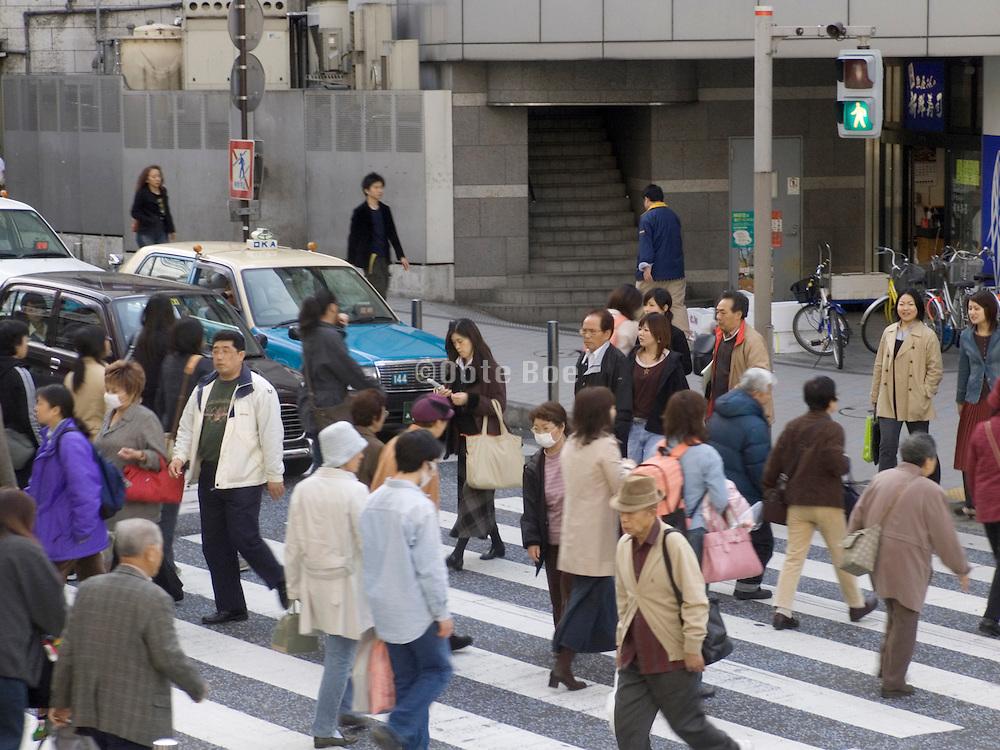 people crossing a street at a zebra near the train station in Yokosuka