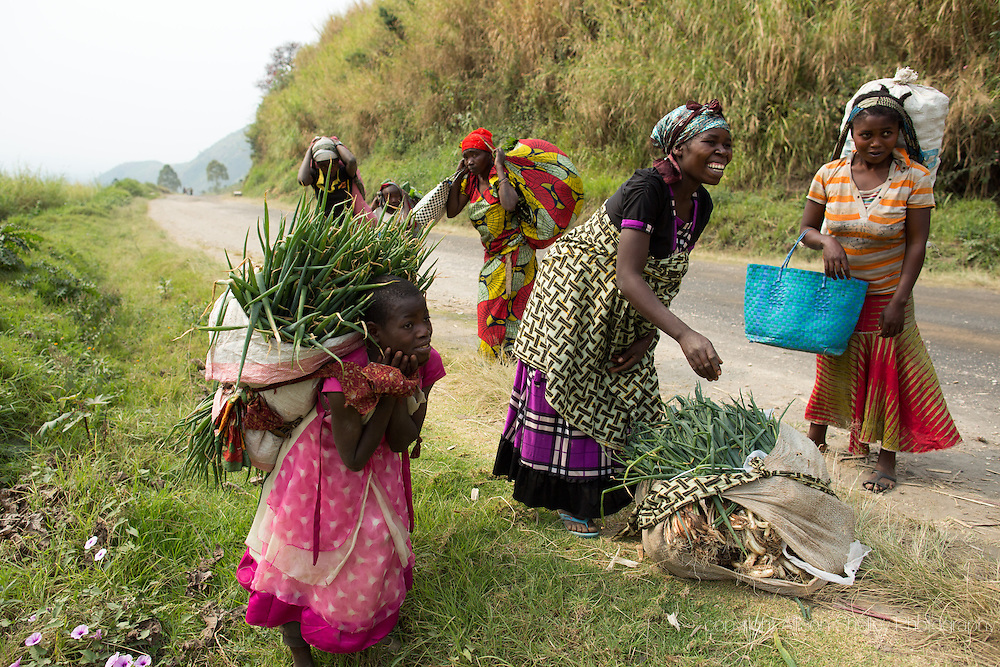 """Nearly nine months pregnant, Arietti Toyota prepares to pick up her bundle of onions after selling to a woman on the road while on her daily four hour journey to market with her daughter Yvette, 11, center, near the village of Mushake, North Kivu, in the Democratic Republic of Congo, July 23, 2014.  Arietti said that her fourth and fifth births happened during the war.  She walked two hours to the hospital to deliver, once during heavy bombardment.  """"When they were shooting, my baby was jumping"""".  She says that she will give birth """"wherever God likes."""""""