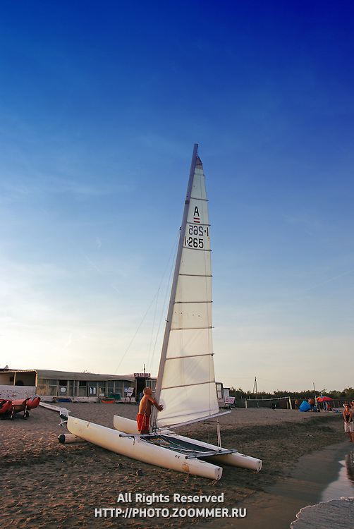 Tweendeck (catamaran) with sail on the beach