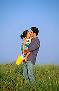 Father gets a kiss from his daughter while standing in the dune grass by the beach.