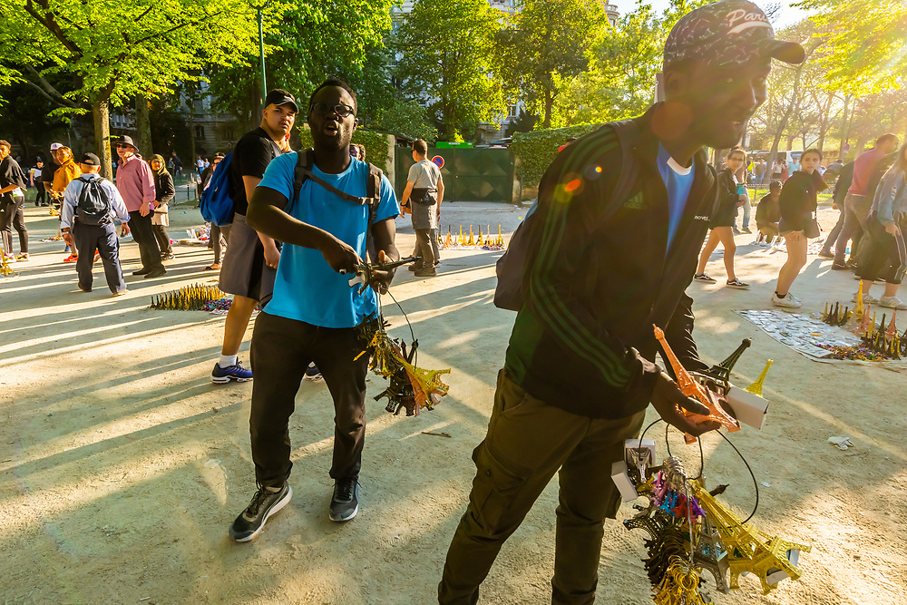 African immigrants illegally selling Eiffel Tower souvenirs outside the tower, Paris, France.