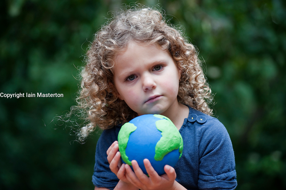 young girl holding a model of planet Earth and showing some concern for future