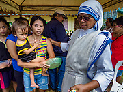 29 JANUARY 2018 - CAMALIG, ALBAY, PHILIPPINES:  A nun with the Missionaries of Charity helps an evacuee from Barangay Gapo in a small shelter for people evacuated from Mayon volcano in Camalig. The Missionaries of Charity visited the shelter to hand out food and clothes. A woman at the shelter said they were out of clean drinking water and several people had come down with diarrhea and other stomach ailments. There are only 206 people at the shelter, many of the shelters have over 1,000 residents. Mayon volcano's eruptions continued Monday. At last count, more 80,000 people have been evacuated from their homes of the slopes of the volcano and are crowded into shelters in communities outside of the danger zone.   PHOTO BY JACK KURTZ