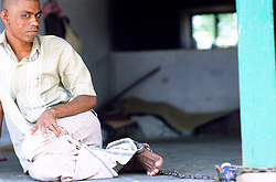 Tamil Nadu, INDIA. March1994..A young man who has his head shaved is chained to the wall..This is the fate awaiting those, who the locals believe are possessed by evil spirits.