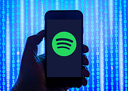 Person holding smart phone with Spotify music streaming logo displayed on the screen. EDITORIAL USE ONLY