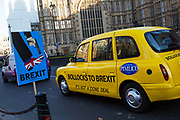 A Brexit placard outside Houses of Parliament, showing a smartly dressed person holding a gun to a shoe in the Union Jack colours, with a Bollocks to Brexit taxi driving past on the 13th December 2018 in Central London in the United Kingdom.