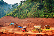 14 MARCH 2013 - ALONG HIGHWAY 13, LAOS:  Construction equipment works on a car park being built to accommodate traffic from China near the end of Highway 13 in the Boten Special Economic Zone. The SEZ is in Laos immediately south of the Lao Chinese border. It has turned into a Chinese enclave but many of the businesses struggle because their goods are too expensive for local Lao to purchase. The Lao businesses on the site, salt evaporation factories, will have to relocate when the parking area is finished. Some of the hotels and casinos in the area have been forced to close by the Chinese government after reports of rigged games. The paving of Highway 13 from Vientiane to near the Chinese border has changed the way of life in rural Laos. Villagers near Luang Prabang used to have to take unreliable boats that took three hours round trip to get from the homes to the tourist center of Luang Prabang, now they take a 40 minute round trip bus ride. North of Luang Prabang, paving the highway has been an opportunity for China to use Laos as a transshipping point. Chinese merchandise now goes through Laos to Thailand where it's put on Thai trains and taken to the deep water port east of Bangkok. The Chinese have also expanded their economic empire into Laos. Chinese hotels and businesses are common in northern Laos and in some cities, like Oudomxay, are now up to 40% percent. As the roads are paved, more people move away from their traditional homes in the mountains of Laos and crowd the side of the road living off tourists' and truck drivers.    PHOTO BY JACK KURTZ