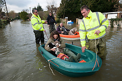 © London News Pictures. 09/02/2014. Wraysbury, UK.  William and Sue O'Brien with their dogs, including three puppies, being rescued from her home which is flooded in Wraysbury, Surrey. The Thames river has hit record levels causing extensive flooding to parts of the southeast of England. Photo credit : Ben Cawthra/LNP