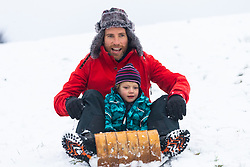 Adam, 45, and his son John, 4, play with their sled as people and their pets enjoy the three inches of snow on Hampstead Heath in North London. Hampstead, London, February 01 2019.