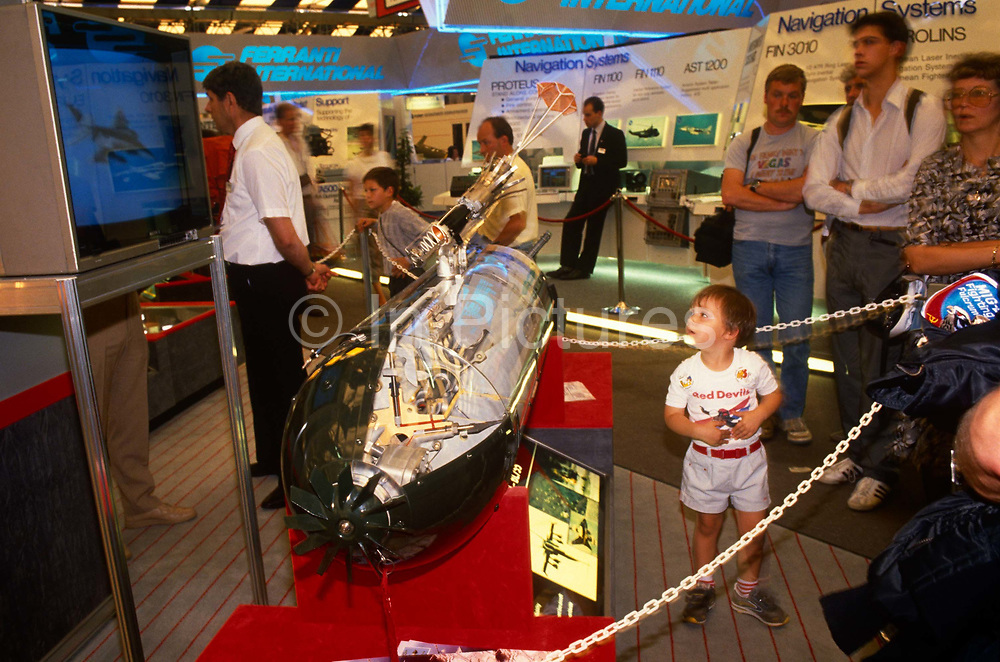 A young child is surrounded by adults as they visit the trade stand of an unnamed manufacturer of a smart bomb that occupies a prominent space at their stand at the Farnborough air show - an expo for the aviation and defence industries. A primitive plastic chain protects the million Pound armament from visitors touching although the bomb will be a non-operational model. A TV screen demonstrates the deadly nature of the guided munition that are typically mounted under the wings of fighter jets - in the days before pilotless drone aircraft.