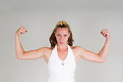 Strong housewife / mother flexes her arm muscles