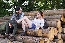 Young couple sitting on woodpile and talking, Bavaria, Germany