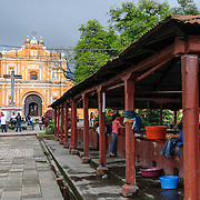 The burnt sienna colored Iglesia en San Pedro las Huertas, about 15 minutes away from Antigua, Guatemala. At right are communial washing areas.