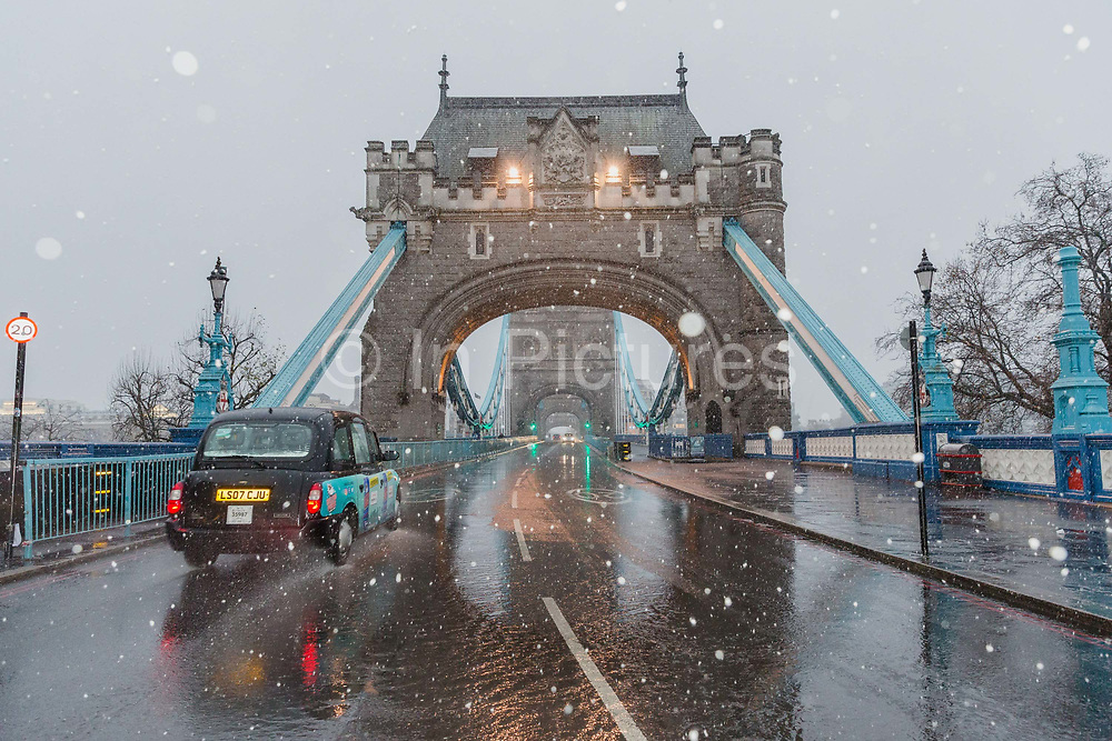 A black cab taxi travels across Tower Bridge during a heavy snow shower on December 10th, 2017. Much of the UK has been hit by heavy snow and The Met Office have issued a yellow weather warning for snow and ice across most of the United Kingdom.