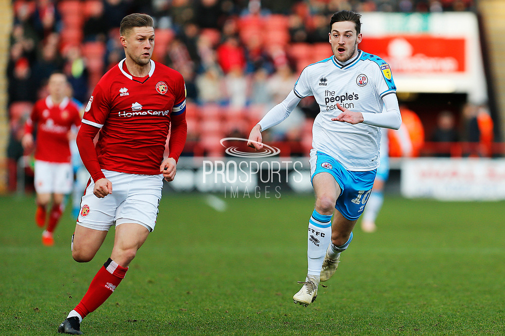 Ashley Nadesan chases the ball with James Clarke during the EFL Sky Bet League 2 match between Walsall and Crawley Town at the Banks's Stadium, Walsall, England on 18 January 2020.