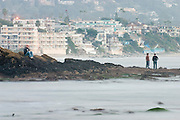 Beachgoers relax into the evening on the rocky shore of Laguna Beach, California.