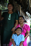 Eugenia Sho, 48, cacao grower from San Antonio, poses for a photograph outside her home with two of her 13 children. Toledo Cacao Growers' Association (TCGA), San Antonio, Toledo, Belize. January 28, 2013.