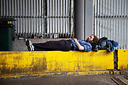 Travelling man lies sleeping on a yellow wall at Victoria Station in Central London.