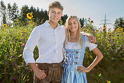 Teenage couple in front of sunflower field, Bavaria, Germany