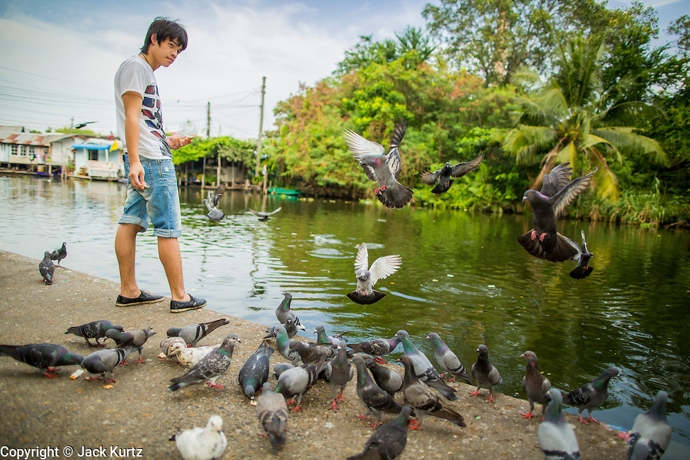 04 JANUARY 2012 - BANGKOK, THAILAND:  A man makes merit by feeding pigeons at Wat Mahabut in eastern Bangkok. The temple was built in 1762 and predates the founding of the city of Bangkok. Just a few minutes from downtown Bangkok, the neighborhoods around Wat Mahabut are interlaced with canals and still resemble the Bangkok of 60 years ago. Wat Mahabut is a large temple off Sukhumvit Soi 77. The temple is the site of many shrines to Thai ghosts. Many fortune tellers also work on the temple's grounds.   PHOTO BY JACK KURTZ