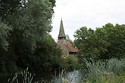 All Saints Church and view alongside the River Chelmer at Utling, England, United Kingdom. All Saints, the village church, has been standing since 1150, with a major restoration taking place in the 1870s. The church was once a place of pilgrimage ranking with other famous shrines.