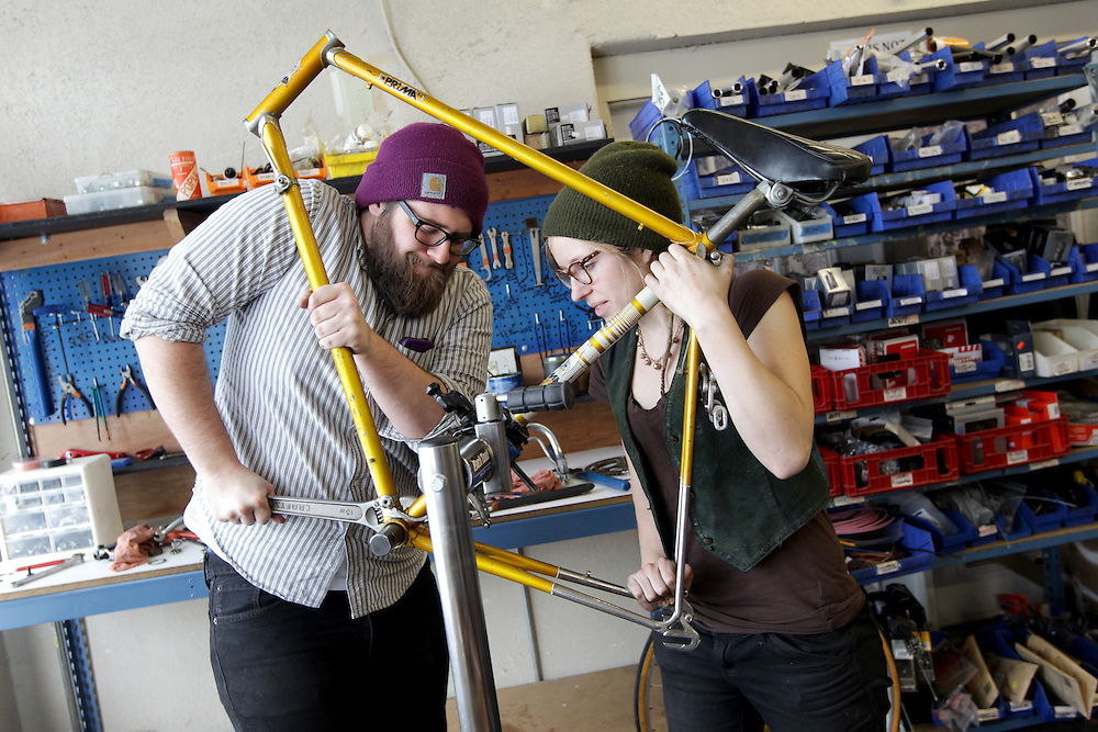 Shop specialist Andrew Dammer, 22, left, and assistant manager Alice Brandt, 23, dismantle a donated bicycle at Express Bike Shop in St. Paul, Minnesota.  Dammer, a former apprentice, also works in marketing for the Youth Express organization.