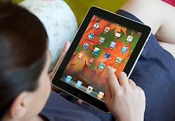 Woman using an iPad tablet computer at home